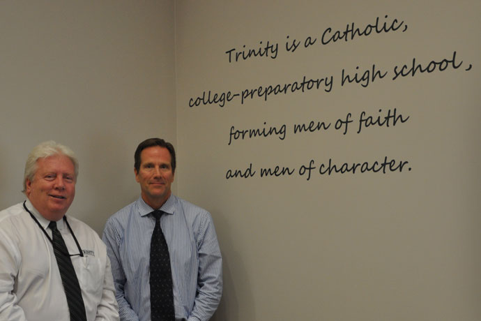 """Trinity High School President Dr. Robert J. Mullen, left, and Principal Dan Zoeller stand next to the words of the school's mission statement last week. The pair said the words """"forming men of faith and men of character"""" served as a guidepost when they instituted a school-wide drug-testing policy two years ago. (Record Photo by Jessica Able)"""