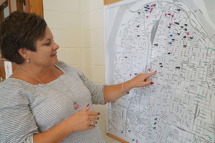 Heidi Hamilton, executive director of Community Catholic Center, pointed to a map showing the number of families served by the center. The black thumb tacks represent families who have been in the program for two or more years. The pink thumb tacks represent families new to the program this school year. (Record Photo by Ruby Thomas)
