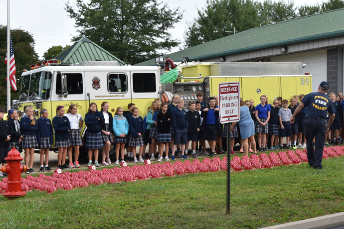 Photo Special to The Record St. Aloysius remembers Sept. 11 Sixth- and seventh-grade students from St. Aloysius School in Pewee Valley, Ky., visited the Pewee Valley Fire Protection District, where all firefighters are volunteers, to commemorate the terrorist attacks of Sept. 11, 2001. The students learned from the firefighters about the 343 firefighters who lost their lives that day. The helmets, in the foreground, represent them. The students also gathered around the flagpole and observed a moment of silence at 9:03 a.m, when Flight 175 crashed into the South Tower of the World Trade Center on Sept. 11. It was the second of two hijacked planes to strike the towers.