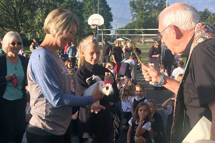 Father Joseph Graffis blessed a pair of guinea pigs belonging to Katie Chase, left, and her daughter Caitlin, a fifth-grader at Our Lady of Lourdes School. Our Lady of Lourdes Church held the blessing on Sept. 28. The blessing of the animals is a tradition tied to the feast of St. Francis of Assisi, patron of animals. The school's first-graders led the service with Scripture and a reminder that St. Francis was a man of peace who cared for all of God's creation. (Photo Special to The Record)