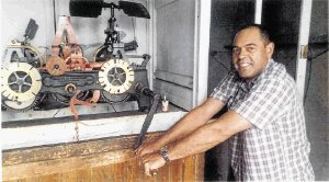 EASY DOES IT: Claude Smith turns the lever that winds up one of the three huge weights that keep the tower clock at the town hall going. Picture: Supplied