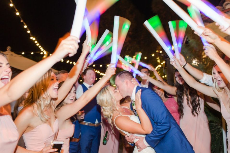 Glow stick grand exit photo. Bride and groom kissing as wedding party waves colorful glowsticks.
