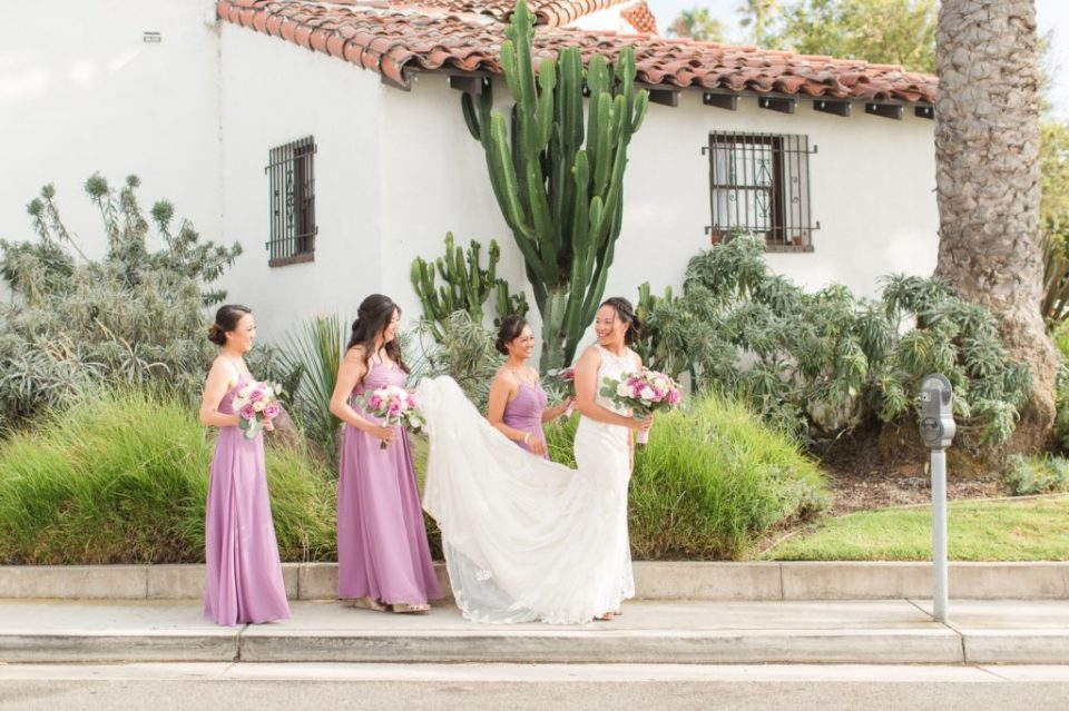 Bride in Esence of Australia dress walking with bridesmaids in purple bridemaid dresses Colorado Wedding Photographer