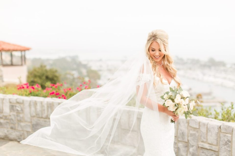 Bride with a veil blowing in the wind in Laguna Beach California. Colorado Wedding Photographer Theresa Bridget Photography