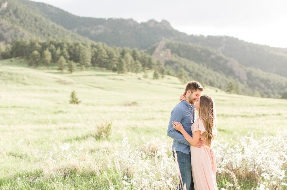Couple kissing in a field during an engagement session at chautauqua park in Boulder Colorado
