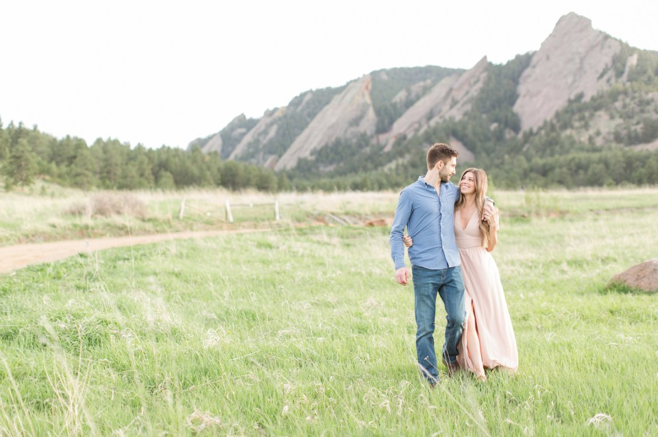 Couple in a field during golden hour. Chautauqua park engagement session in Boulder Colorado