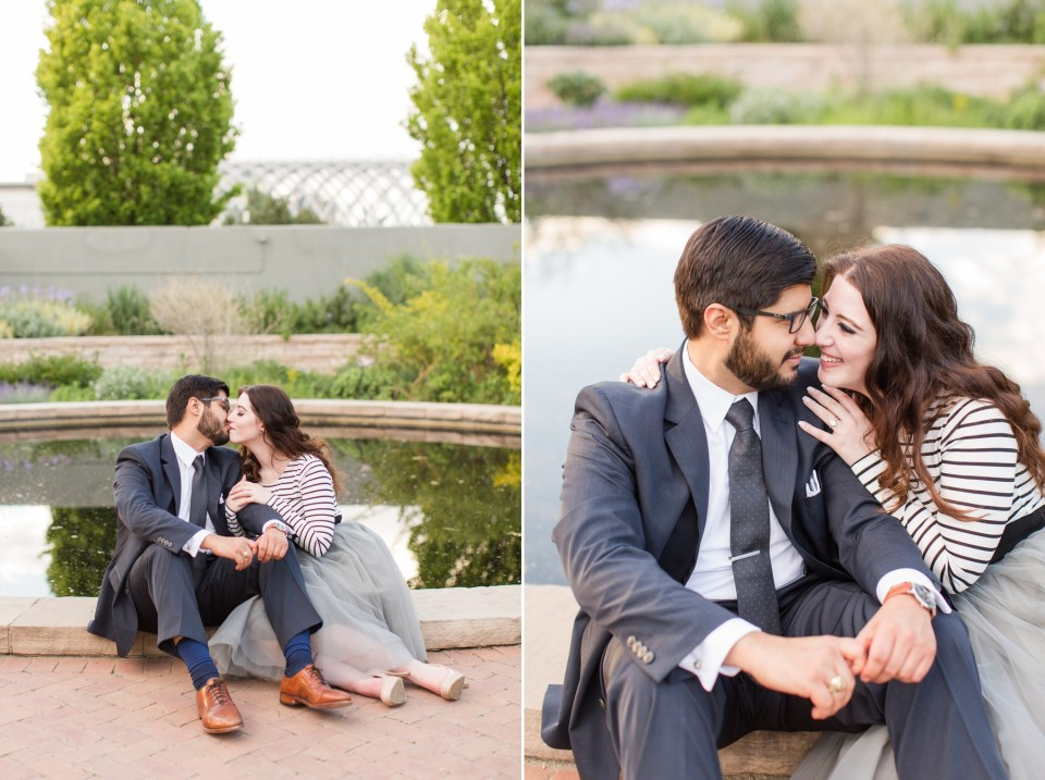 Couple sitting on the ground kissing at the Denver Botanic Gardens.