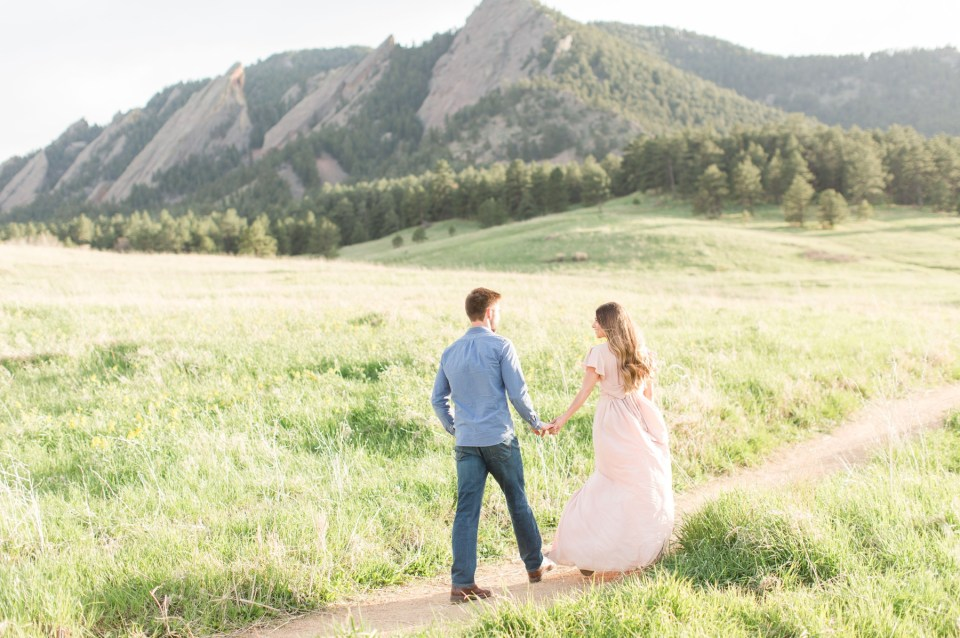 Couple walking in front of the flatirons in Boulder for an engagement session. Colorado wedding photographer