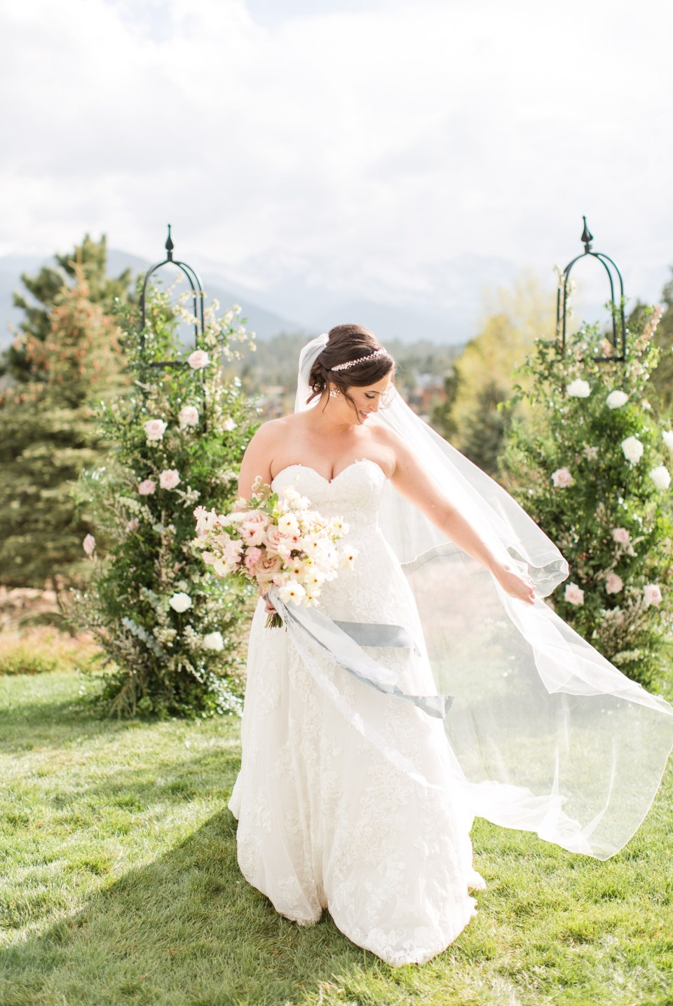 Bride in her wedding dress and veil in front of mountain views at the Stanley Hotel in Estes Park Colorado