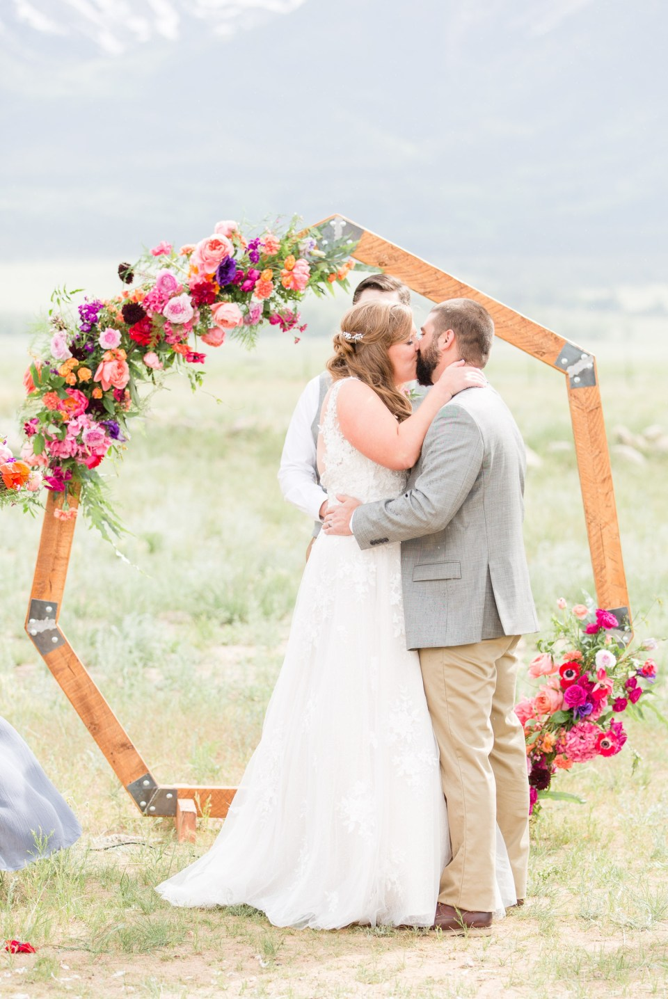 First kiss in front of a hexagon ceremony arch with colorful flowers.