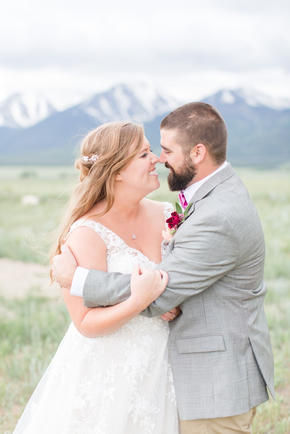 Romantic image of bride and groom in front of a mountain at the barn at Sunset Ranch in Buena Vista Colorado.