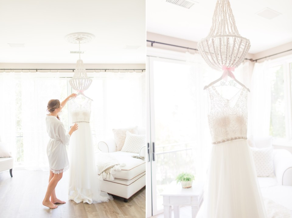 Wedding dress in a clean room handing from a white beaded chandler. Bride looking up at her wedding dress before getting ready, candid wedding morning shot.