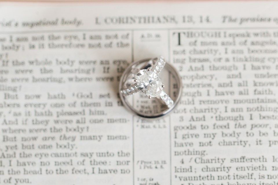Engagement ring along with wedding rings sitting on a bible in front of the wedding verse. Corinthians 13
