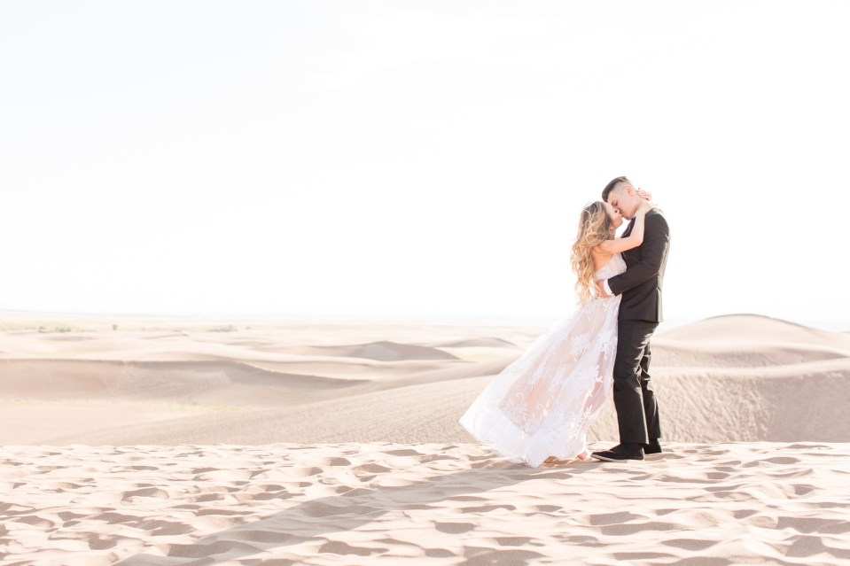 Couple kissing on top of a sand dune at Great Sand Dunes National Park in Colorado. National Park engagement Session