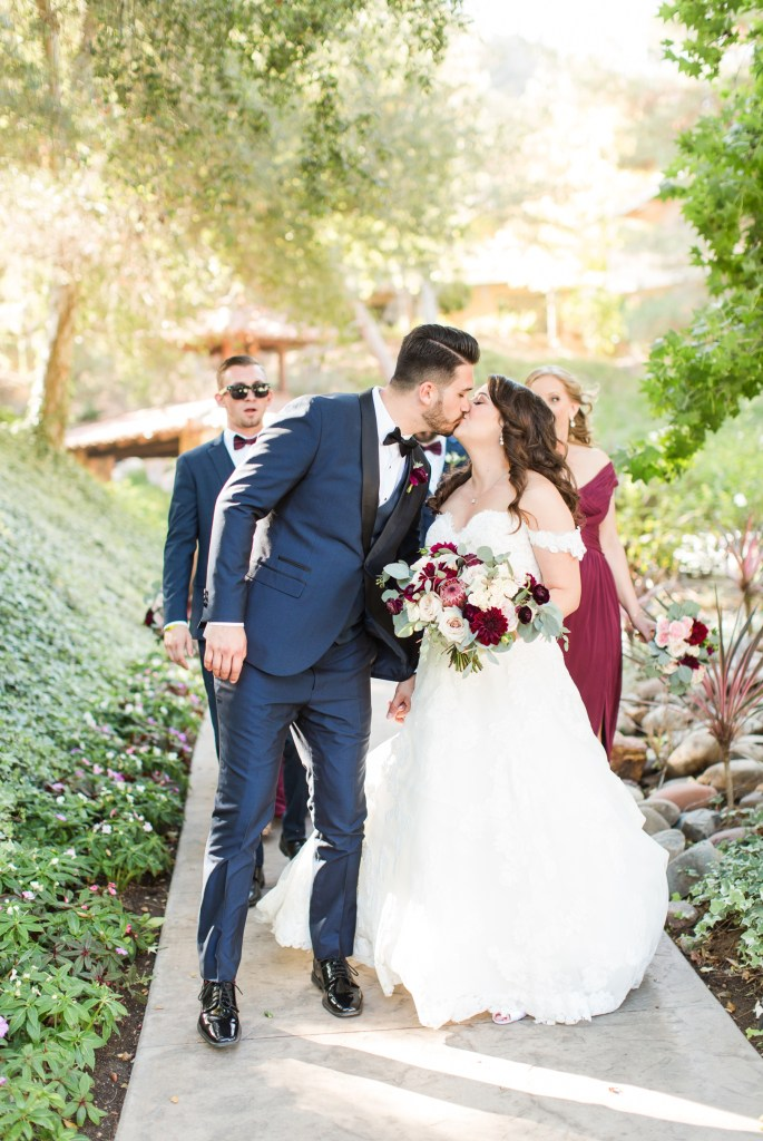 Bride and groom casually kissing in a candid shot on wedding day
