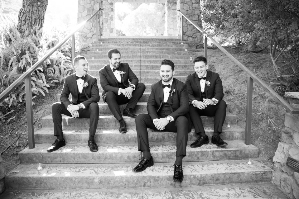 Groom and groomsmen in black and white posing on stairs