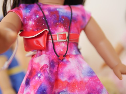 Luciana Vega comes with a necklace with a star on it and a red belt with fanny pack.