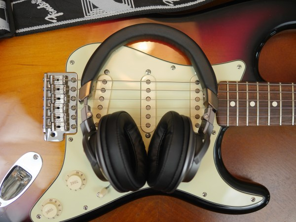 Flat lay photo of Audio Technica headphones with a Fender guitar. 3 Reasons Musical Gifts Make Dads Happy - Theresa's Reviews