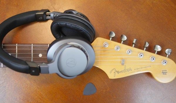 Flat lay photo of Audio Technica headphones with a Fender guitar and pick. 3 Reasons Musical Gifts Make Dads Happy - Theresa's Reviews