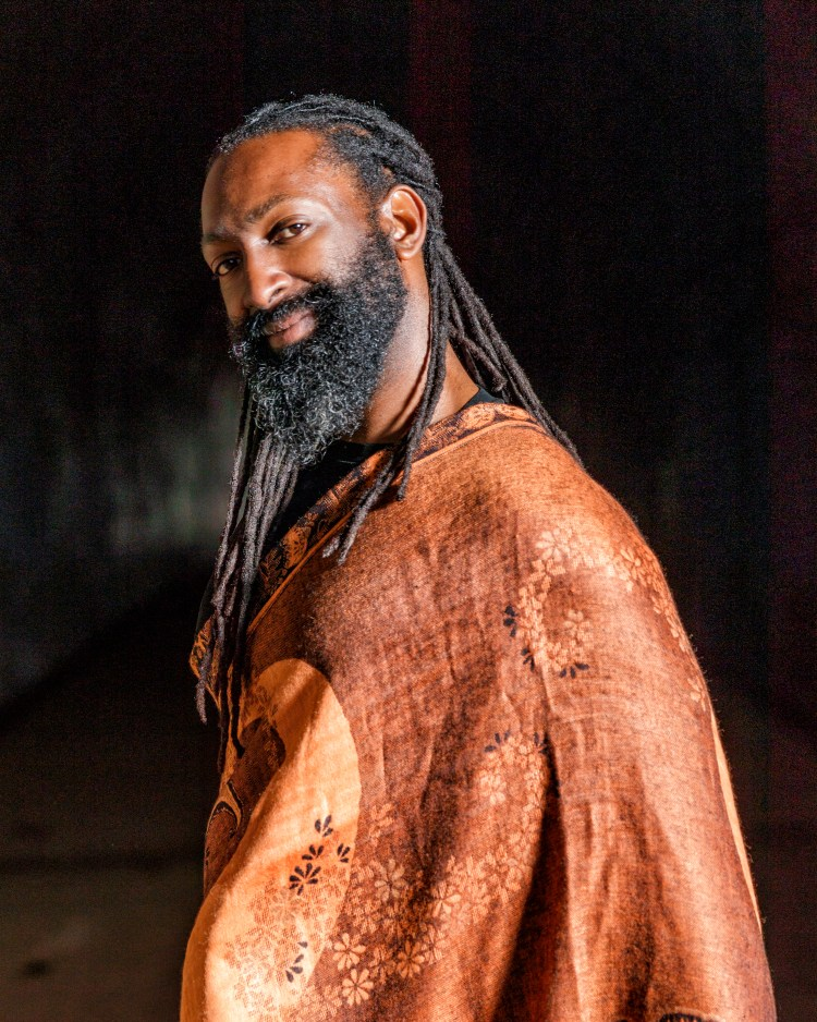 A headshot of Antoine Hunter with Ebony dreadlocks in a low half braid and a full beard.