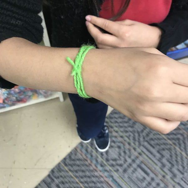 student showing string on wrist