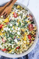 Pasta Salad with fresh basil, grilled corn, cherry tomatoes, and feta cheese with a lemony vinaigrette.