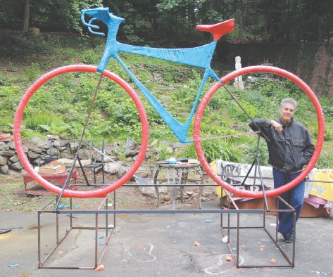 Jerry Beck, founder and artistic director of the Revolving Museum, shows off the 9 1/2-foot-tall, 12-foot-long bicycle he and a group of students built to promote the upcoming Longsjo Classic.COURTESY REVOLVING MUSEUM
