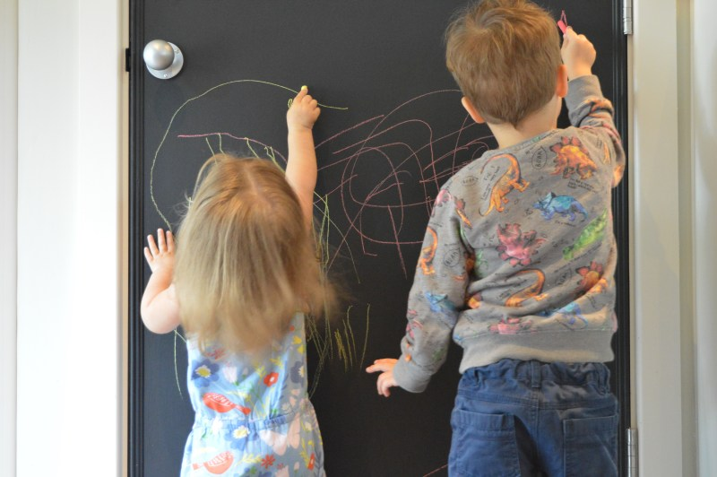 Toddler drawing on a chalkboard at Center Parcs Woburn Forest