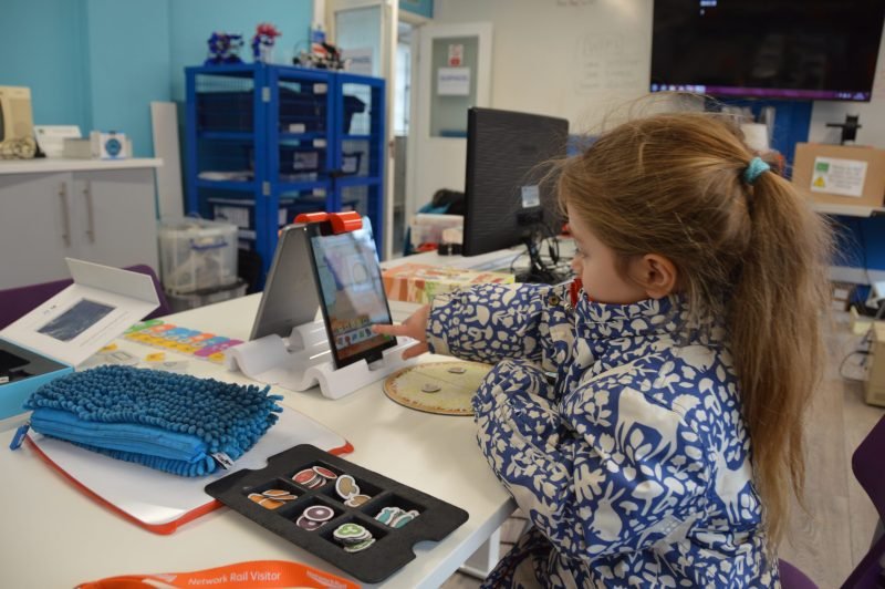 A little girl using an iPad in the BBC classroom
