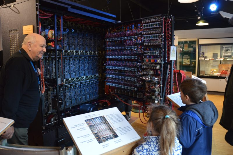 Children looking at the back of the Turing Bombe to see how it works