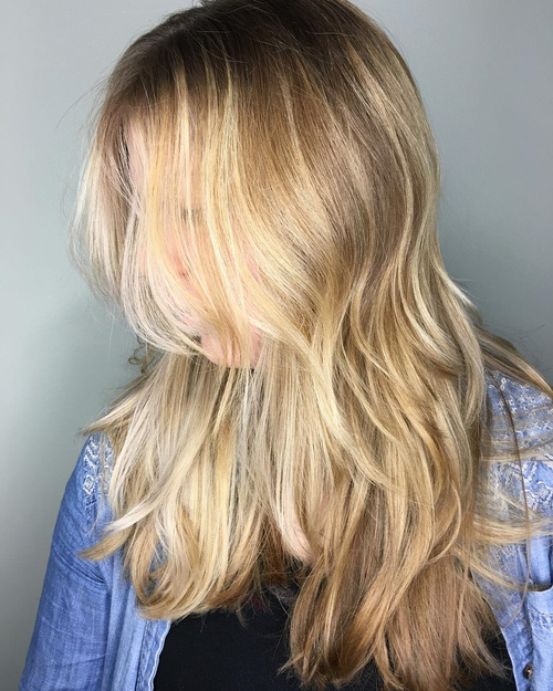 long blonde layered hairstyle with balayage
