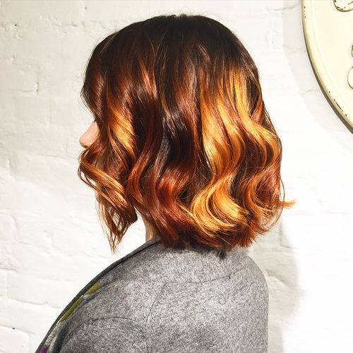long wavy red bob with golden blonde balayage