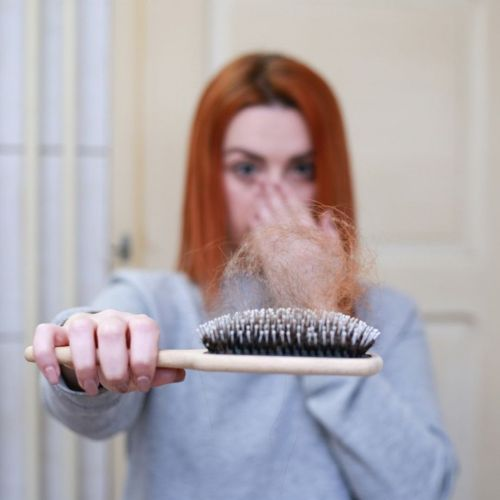 Woman Holding a Brush with Many Lost Hairs