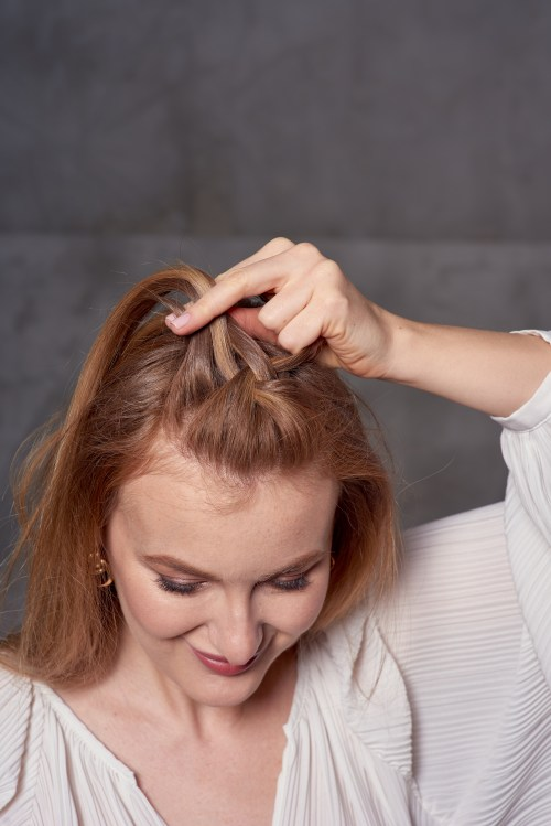 Woman Showing How to French Braid Your Own Hair