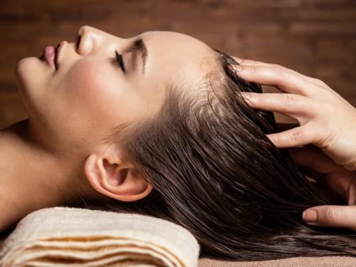 Woman in Spa Enjoying a Scalp Massage