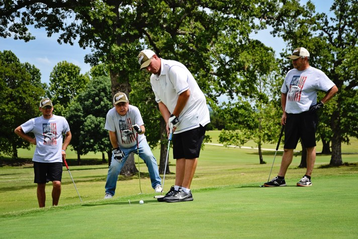 four golfers putting at Par 4 the Horse tournament