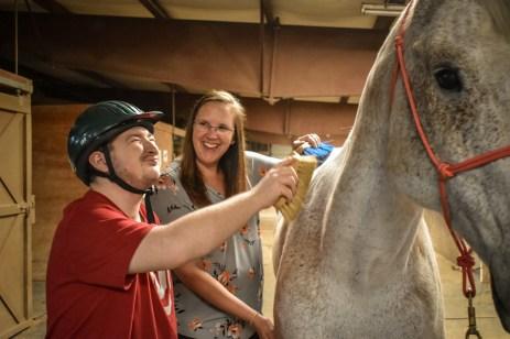 volunteer helping student groom gray horse