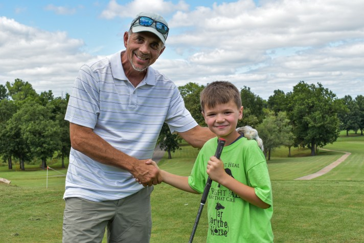 golfer shaking hands with young volunteer