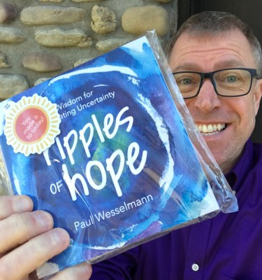 "Photo of Paul, The Ripples Guy holding a small package that says, ""Ripples of Hope"""