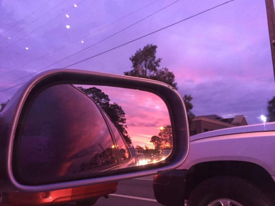 Bright purple sunset sky in the rearview mirror