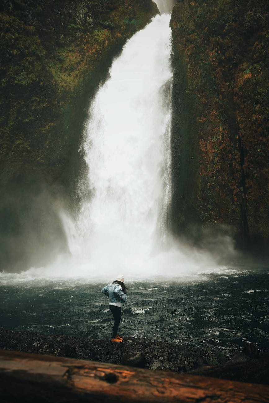 person in blue jacket and black pants standing on rock near waterfalls