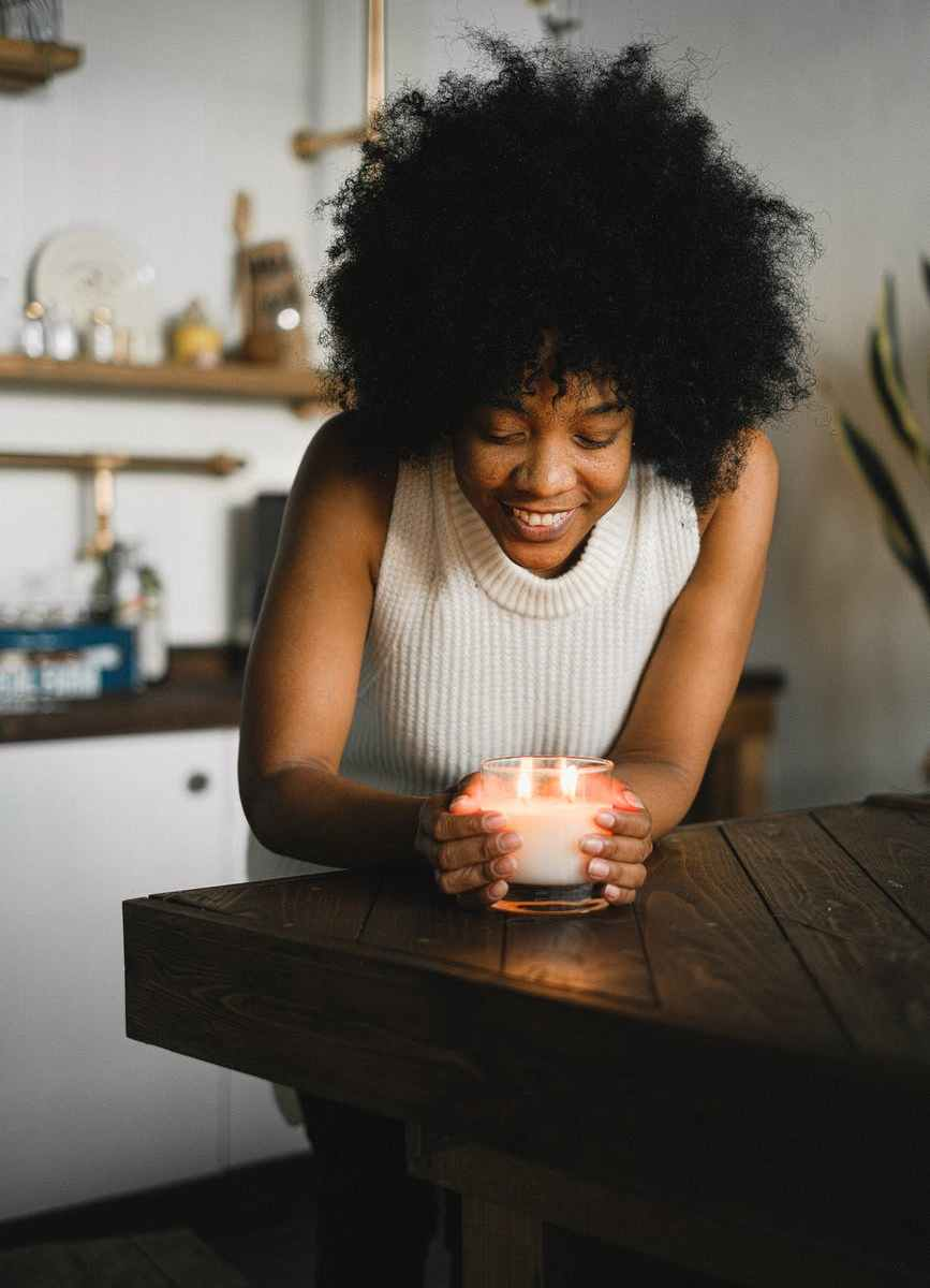 ethnic woman with aromatic candle at home