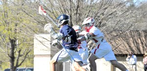 Raider Andrew Proctor (in white) battles a Covenent attacker Friday afternoon as the Eagles rolled to the 15-4 lacrosse win at Thomas Field.