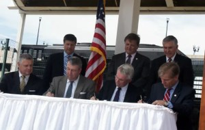 Roanoke Mayor David Bowers (far left) and Governor Bob McDonnell (far right) take part in a signing ceremony at Railside Plaza.