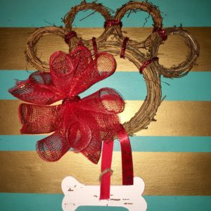 Take your bone shape and a piece of ribbon. Wrap the ribbon around the vine and glue the ends together. DIY Paw Wreath For The Pet Lover