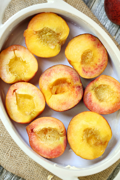 halves of peaches sitting in a baking white baking dish