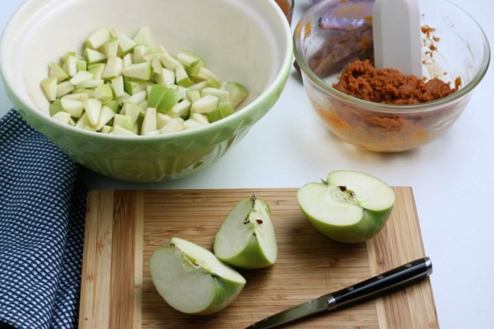 green apples being cut on cutting board