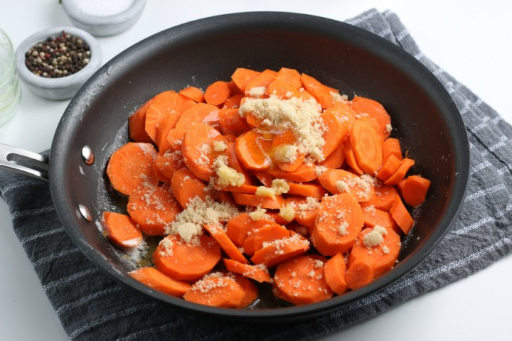 carrots, brown sugar, honey and garlic added to a frying pan