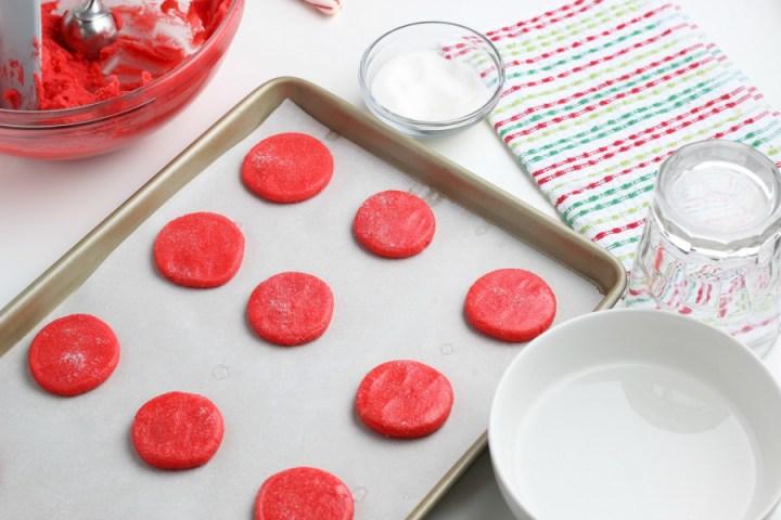 cookie dough balls flattened on a baking sheet