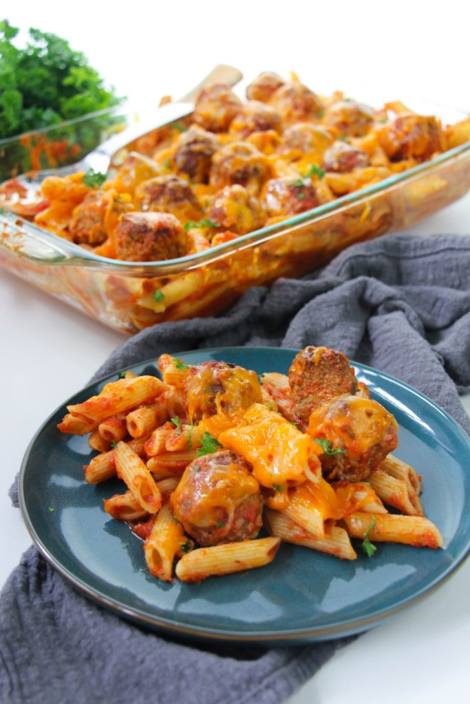 meatball casserole in a baking dish, with a serving of the recipe on a blue plate